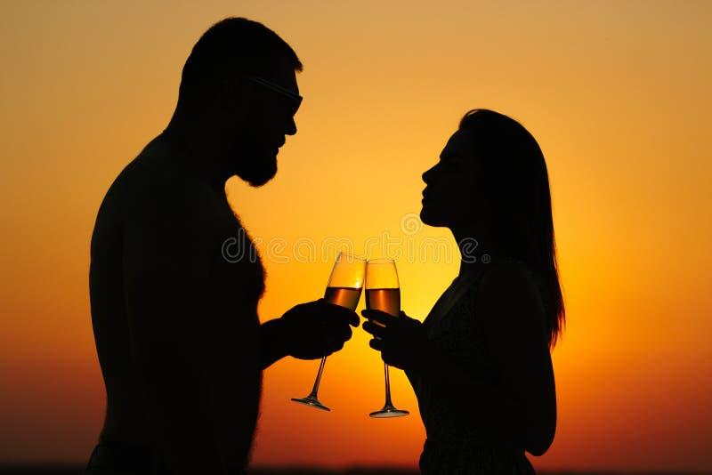 Coppie felici che godono di un bicchiere di vino o di un champagne, siluetta delle coppie in vino bevente di amore dai bicchieri  immagini stock