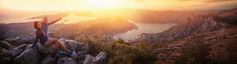 Coppie felici che guardano il tramonto nelle montagne immagini stock