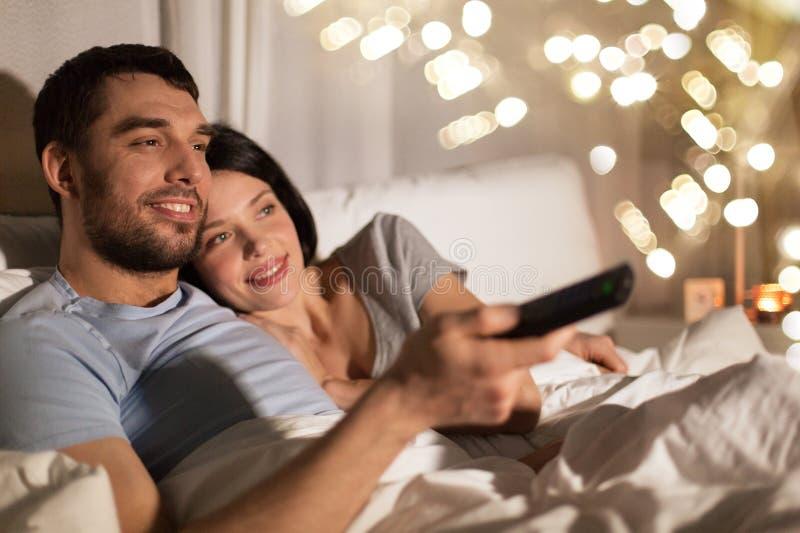 Coppie felici che guardano TV a letto alla notte a casa fotografia stock libera da diritti