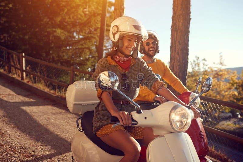 Coppie felici che guidano un motorino e divertiresi fotografia stock