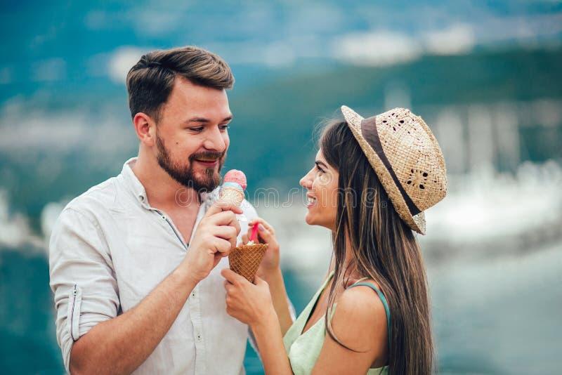 Coppie felici che hanno data e che mangiano il gelato sulla vacanza immagini stock