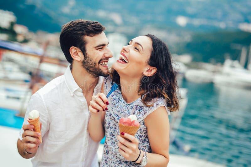Coppie felici che hanno data e che mangiano il gelato sulla vacanza fotografia stock
