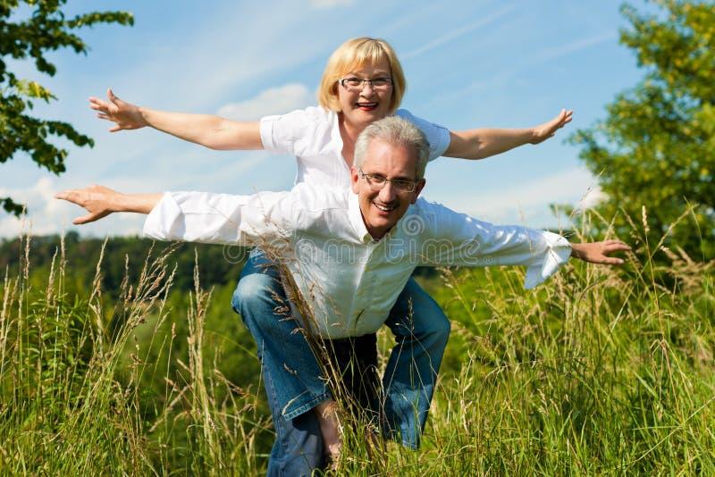 Coppie felici che hanno divertimento all'aperto in estate immagine stock
