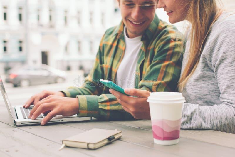 Coppie felici che hanno pausa caffè insieme e che per mezzo dello smartphone immagini stock