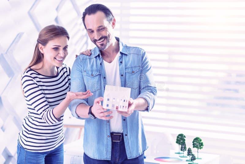 Coppie felici che indicano le case miniatura e che ammirano la progettazione immagine stock libera da diritti