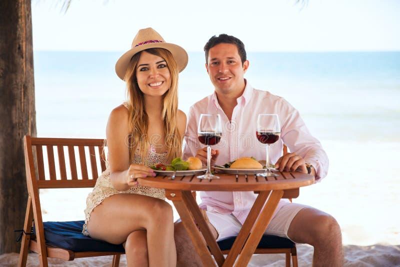 Coppie felici che mangiano pranzo alla spiaggia fotografia stock