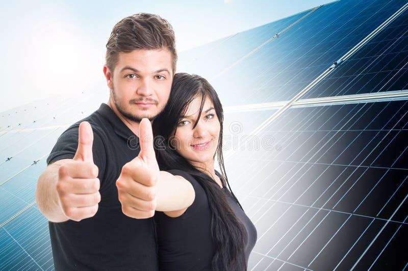 Coppie felici che mostrano come sulla parte posteriore fotovoltaica del pannello di energia solare fotografie stock libere da diritti