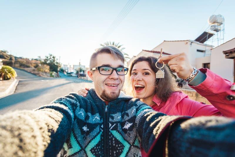 Coppie felici che mostrano le loro chiavi della nuova casa immagine stock