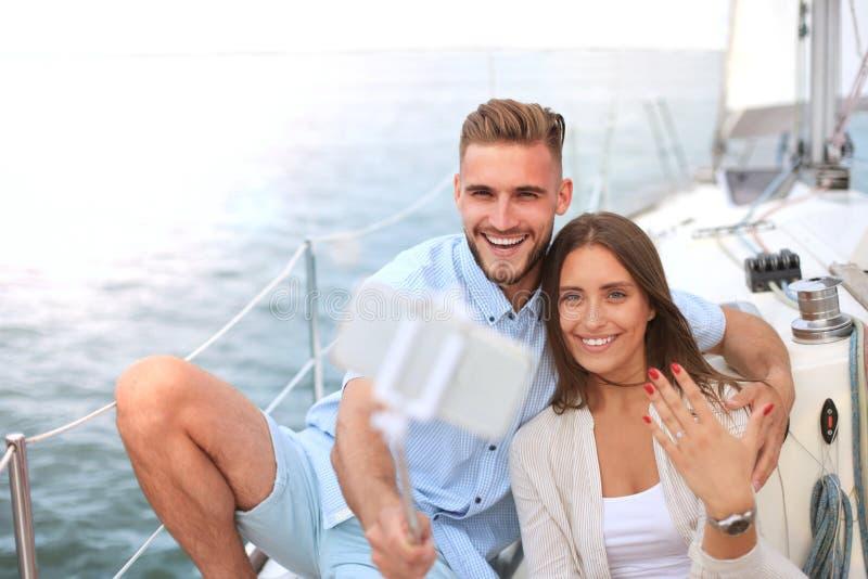 Coppie felici che prendono un selfie dopo la proposta di impegno alla barca a vela, rilassantesi su un yacht al mare immagine stock