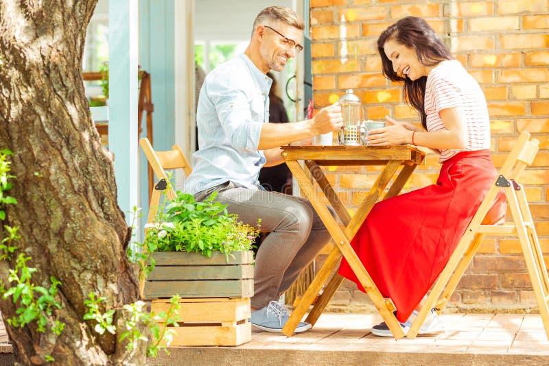 Coppie felici che ridono alla loro data in un caffè fotografie stock