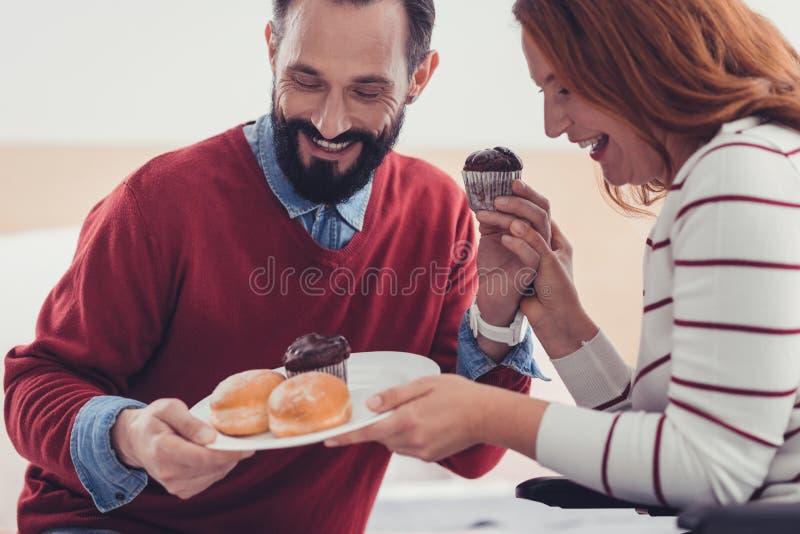Coppie felici che ridono mentre esaminando i dolci sul piatto immagine stock
