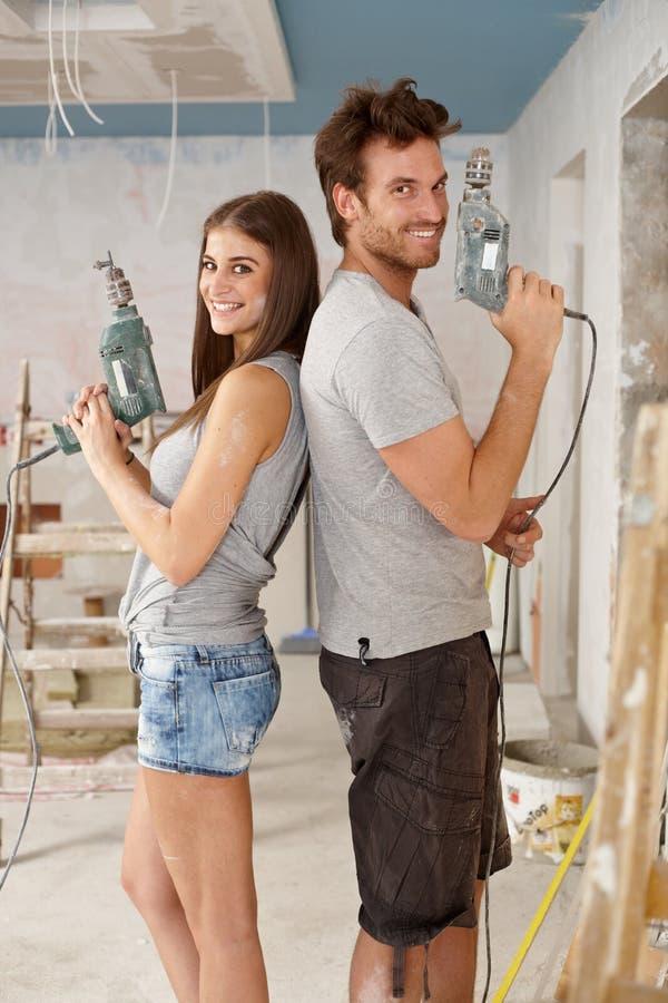 Coppie felici che rinnovano a casa immagini stock libere da diritti
