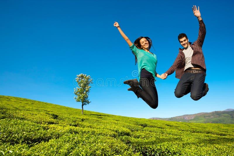 Coppie felici che saltano su fotografia stock