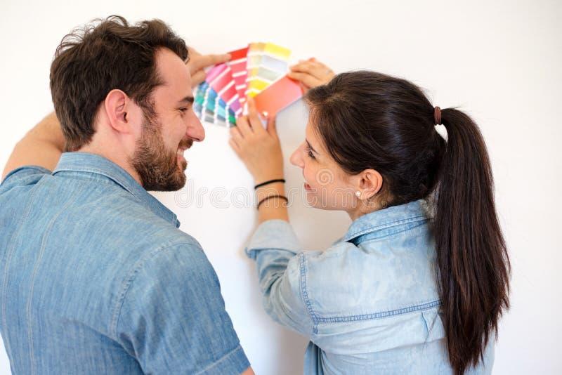 Coppie felici che scelgono i colori per la decorazione che dipinge nuova casa immagini stock libere da diritti