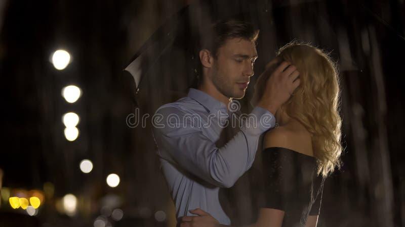 Coppie felici che si abbracciano e che si godono di nell'ambito della pioggia, della passione e dell'amore fotografia stock libera da diritti
