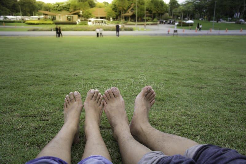 Coppie felici che si rilassano sull'erba verde Coppie che si trovano sull'erba esterna barefoot Maschio e femmina asiatici, in un immagini stock libere da diritti
