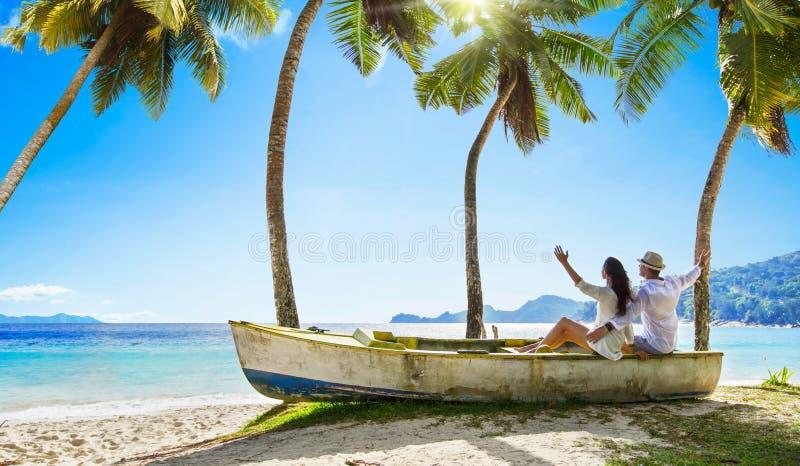 Coppie felici che si rilassano sull'oceano Isola delle Seychelles fotografia stock libera da diritti