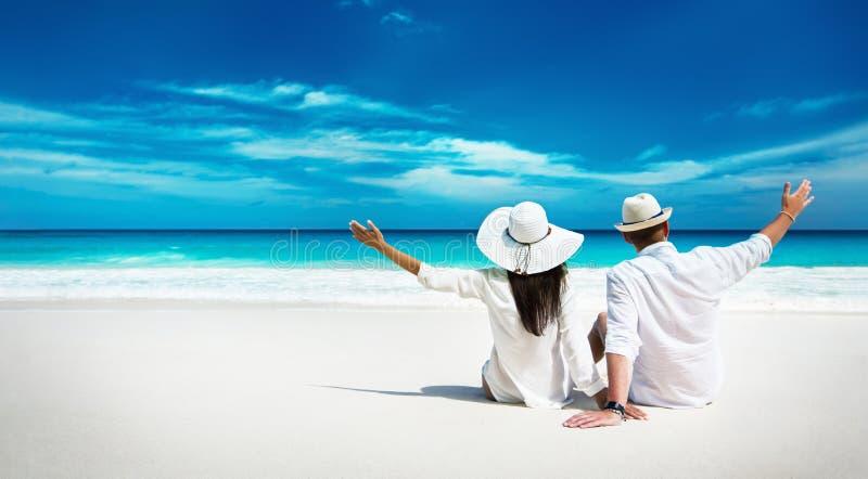 Coppie felici che si rilassano sull'oceano Isola delle Seychelles immagini stock