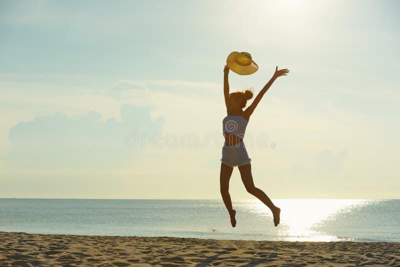 Coppie felici che si rilassano sulla spiaggia all'alba, vista posteriore fotografia stock