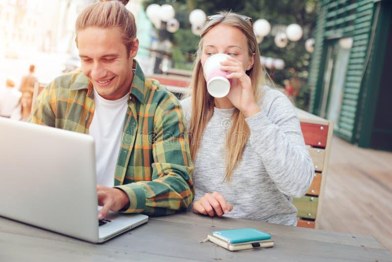Coppie felici che si siedono insieme in caffè della via e che per mezzo del computer portatile, bere della donna fotografia stock libera da diritti