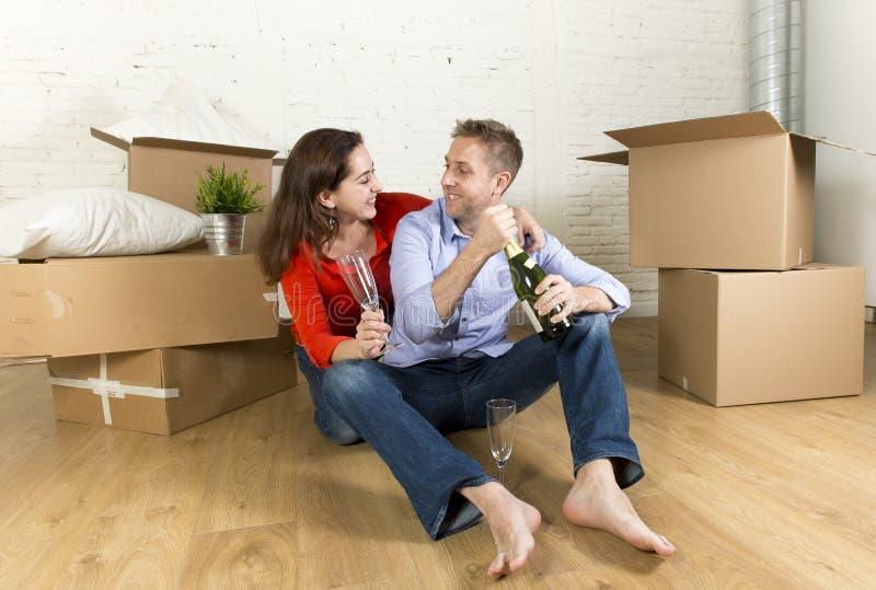 Coppie felici che si siedono sul pavimento che disimballa insieme celebrazione con il pane tostato del champagne che si muove nel fotografie stock libere da diritti