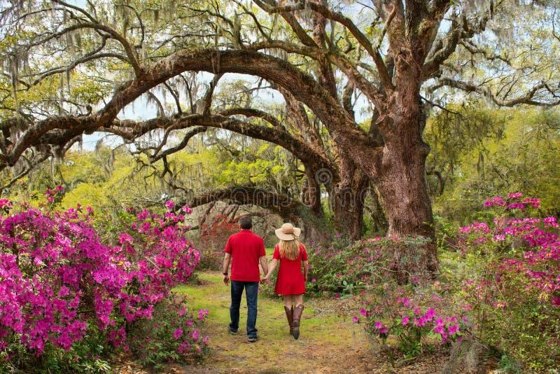 Coppie felici che si tengono per mano camminata nel giardino sul viaggio di fine settimana immagini stock libere da diritti
