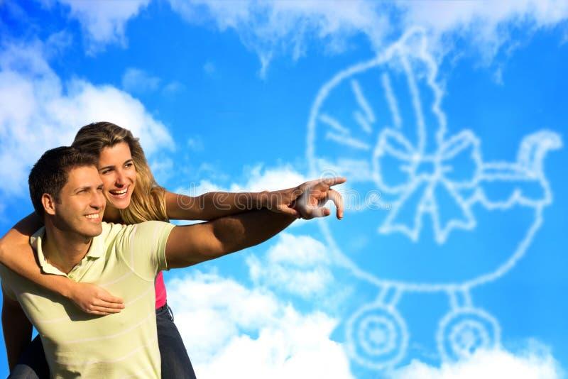 Coppie felici che sognano di un bambino e che indicano le nuvole. fotografia stock