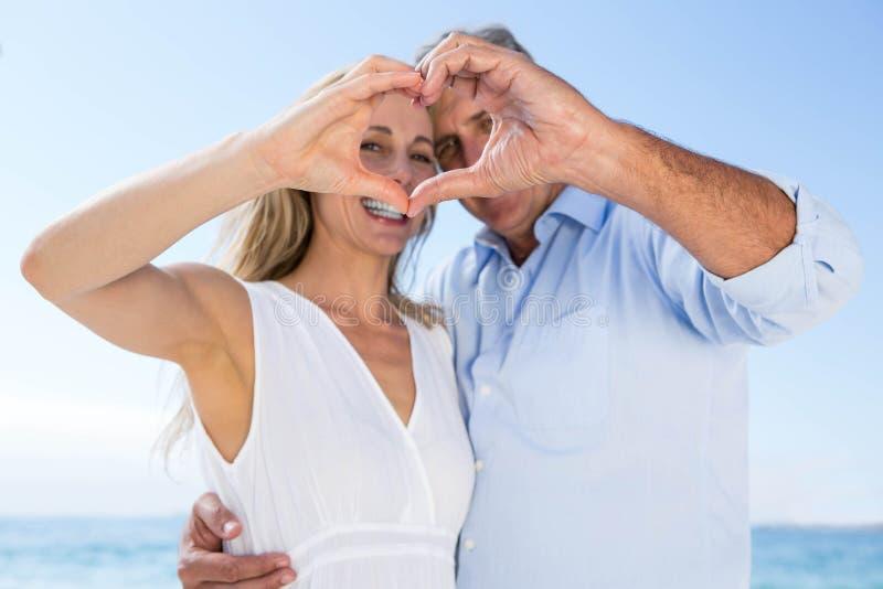 Coppie felici che sorridono alla macchina fotografica e che fanno forma del cuore con le loro mani fotografie stock