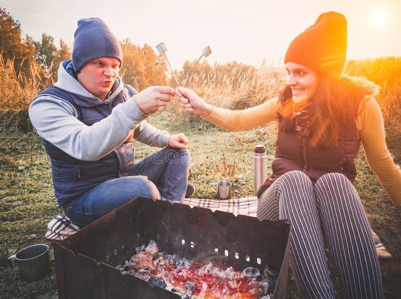 Coppie felici che sorridono e caramelle gommosa e molle dell'arrosto su fuoco di accampamento sulla natura Il resto allegro della fotografia stock