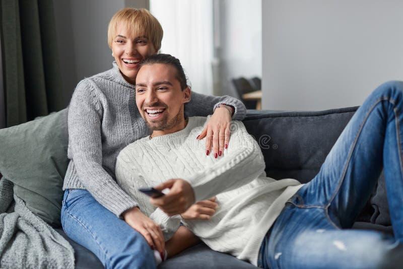 Coppie felici che spendono tempo sul sofà immagini stock
