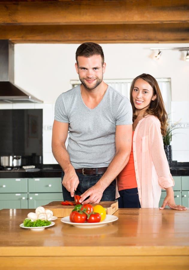 Coppie felici che tagliano le verdure a pezzi al contatore di cucina immagine stock libera da diritti