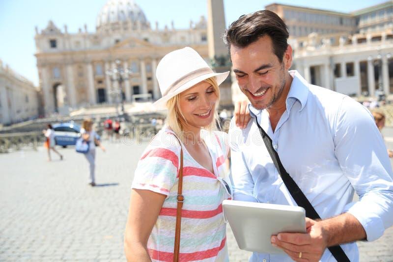 Coppie felici che tengono una compressa in via di Roma immagine stock
