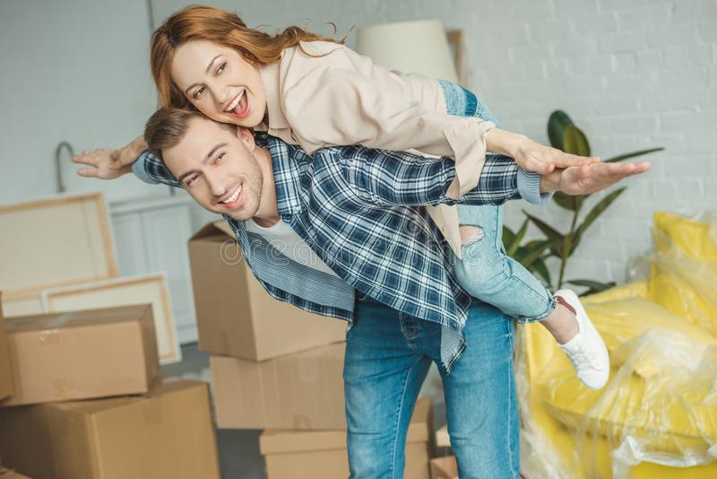 coppie felici che trasportano sulle spalle al nuovo appartamento con le scatole di cartone, fotografia stock