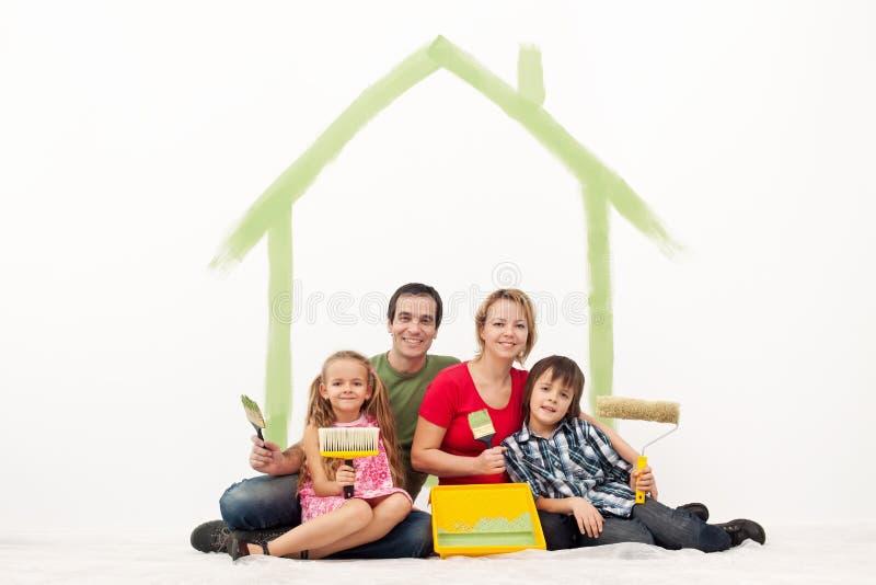 Coppie felici con due bambini che ridipingono la loro casa fotografia stock libera da diritti
