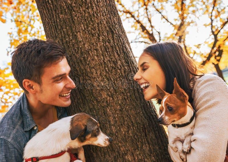 Coppie felici con i cani all'aperto nel parco di autunno immagini stock libere da diritti