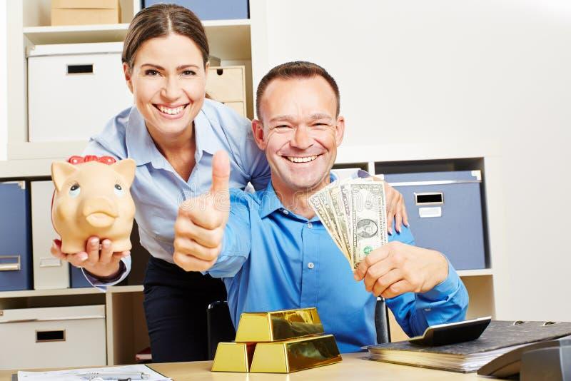 Coppie felici con i soldi e l'oro del dollaro fotografie stock libere da diritti