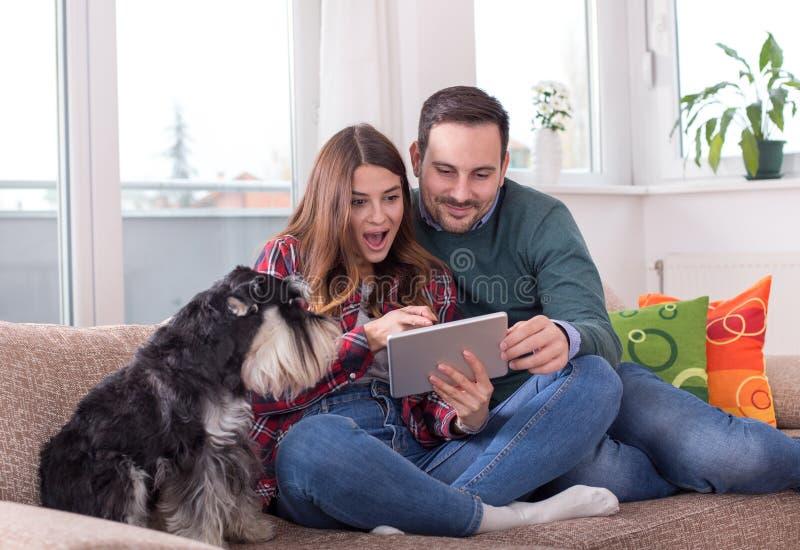 Coppie felici con il cane sul sofà fotografia stock libera da diritti
