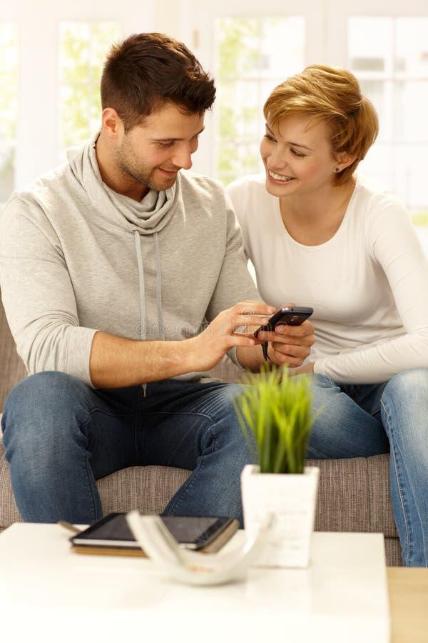 Coppie felici con il cellulare fotografia stock libera da diritti