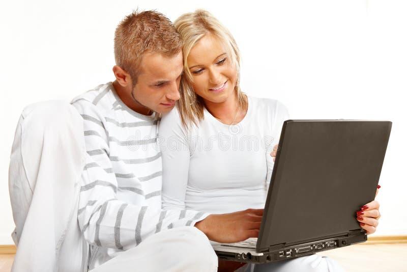 Coppie felici con il computer portatile immagine stock libera da diritti