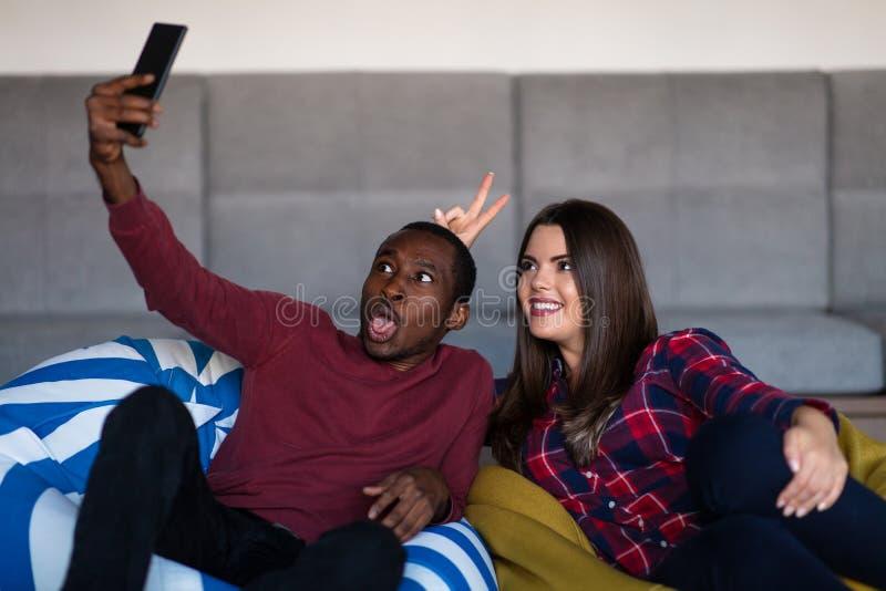 Coppie felici con la compressa e lo smartphone del computer su un sof? fotografie stock