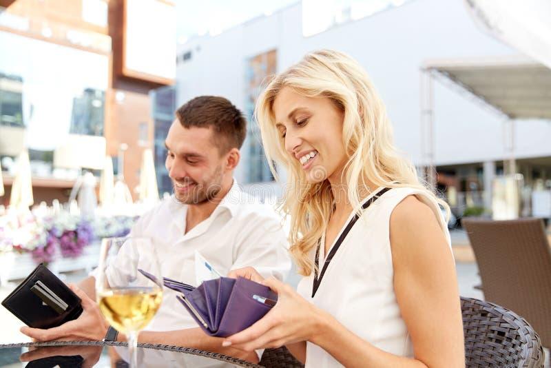 Coppie felici con la fattura di pagamento del portafoglio al ristorante fotografie stock