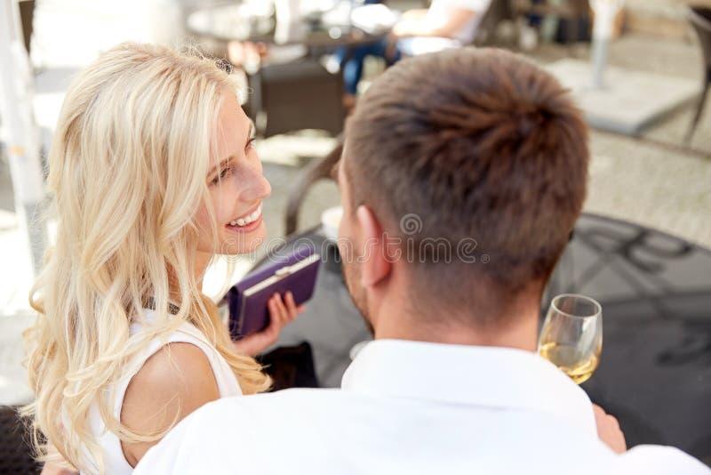 Coppie felici con la fattura di pagamento del portafoglio al ristorante immagini stock