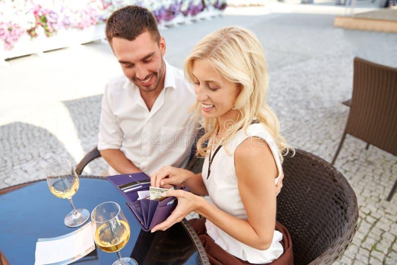 Coppie felici con la fattura di pagamento del portafoglio al ristorante fotografia stock