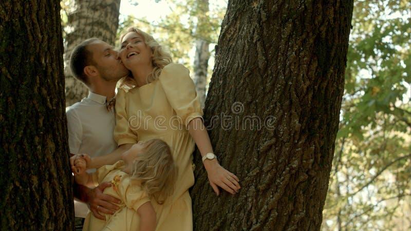 Coppie felici con la sua piccola figlia che bacia sopra un fondo della foresta fotografia stock