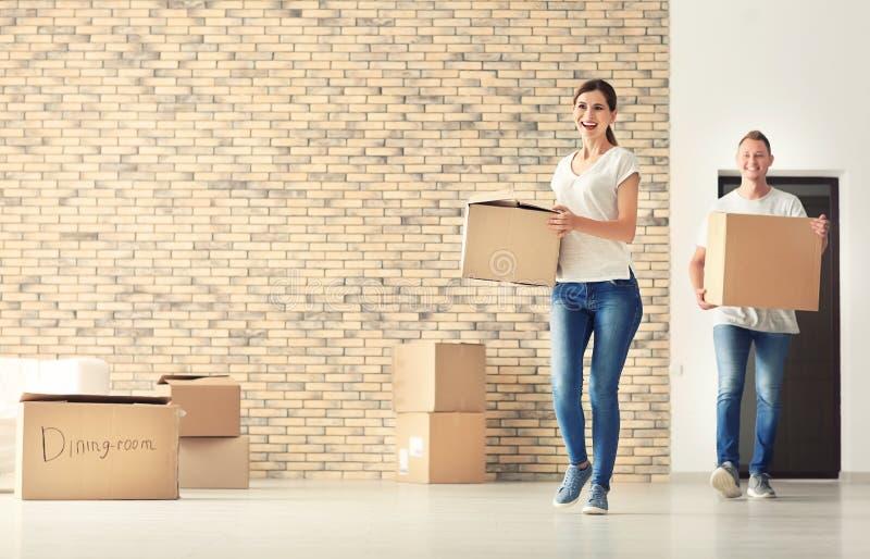 Coppie felici con le scatole di cartone all'interno Entrando nella nuova casa fotografia stock libera da diritti