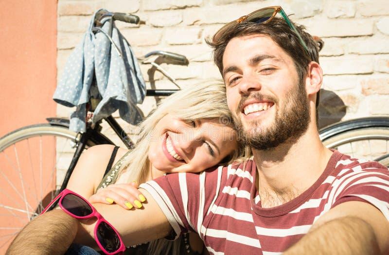 Coppie felici dei pantaloni a vita bassa che prendono selfie al vecchio viaggio della città con la bicicletta fotografia stock