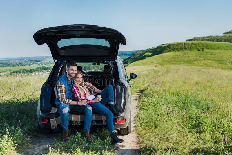 coppie felici dei turisti alla moda con le tazze di caffè che si siedono sul tronco di automobile in rurale fotografie stock libere da diritti