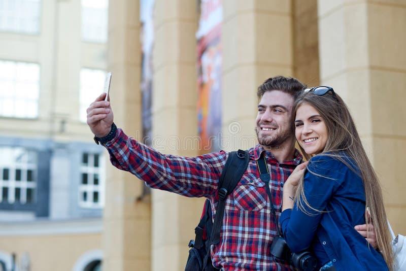 Coppie felici dei turisti che prendono selfie in attrazione della città immagini stock