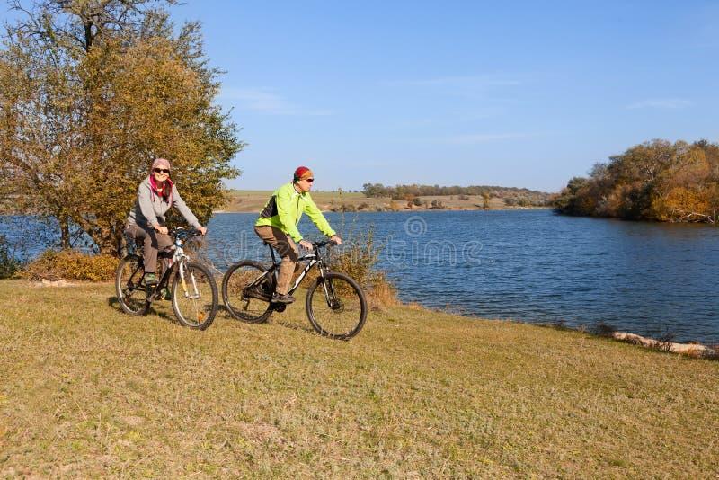 Coppie felici del mountain bike che ciclano all'aperto immagine stock libera da diritti