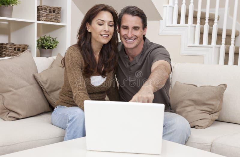 Coppie felici della donna & dell uomo per mezzo del computer portatile